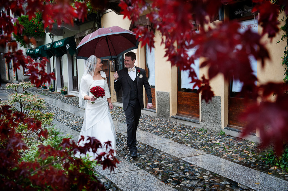 Italian wedding photographers, portfolio, Lake Orta wedding, bride and groom walking in the rain