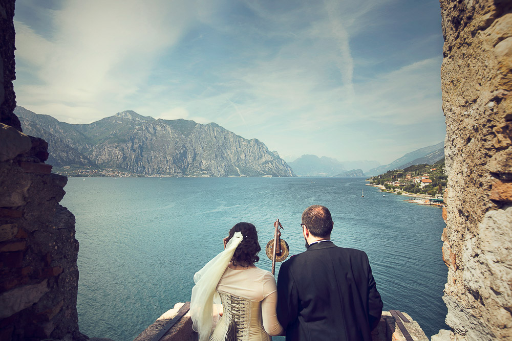 bride and groom looking at the lake from a balcony