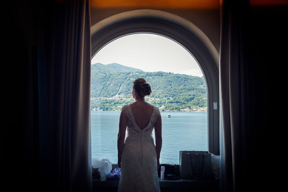The bride is looking at the amazing lake from the window
