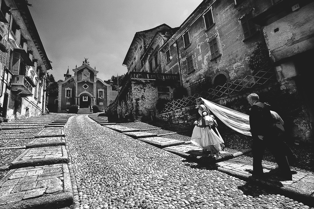 Italian wedding photographers, Lake Orta, bride with her father and flowergirl are going to the church