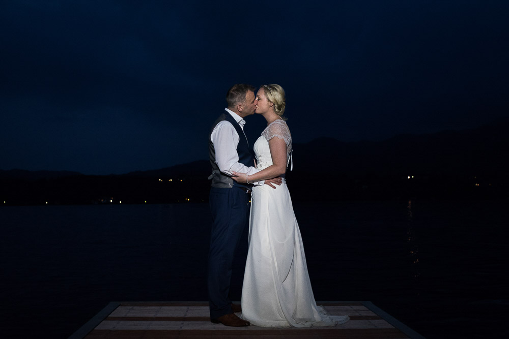 bride and groom kiss on a jetty