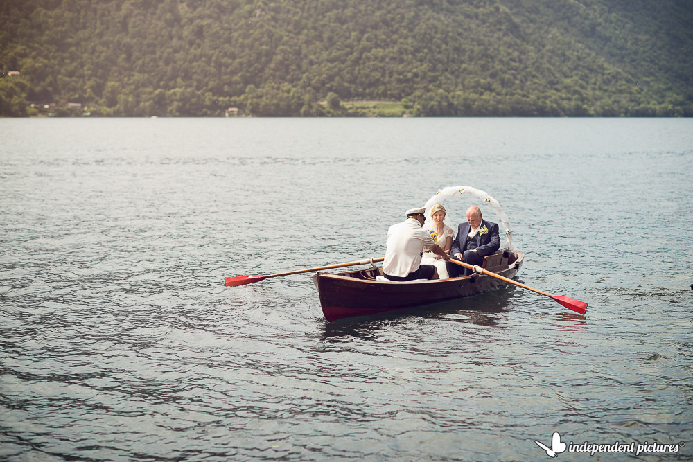 bride and her father on rowing boat reaching the ceremony