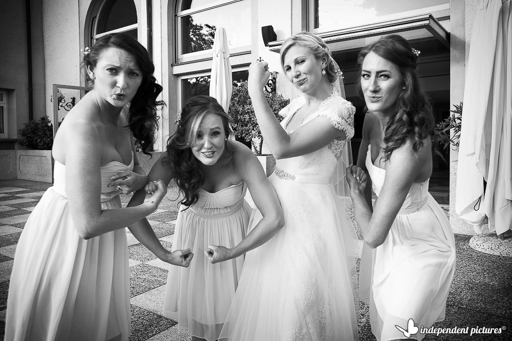 bride and bridesmaids showing muscles