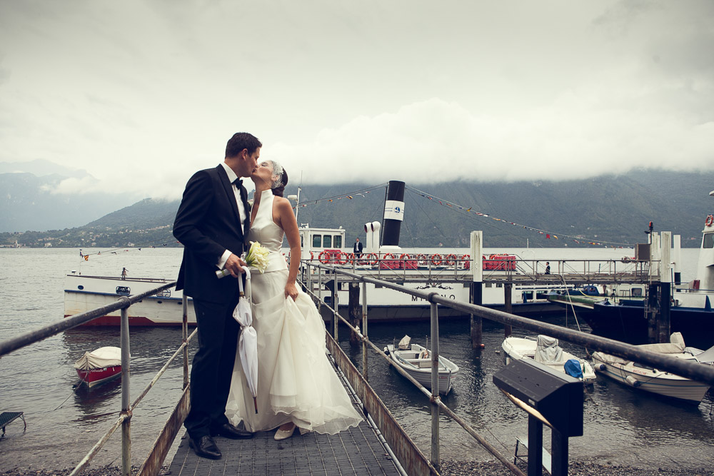 bride and groom kissing on a jetty
