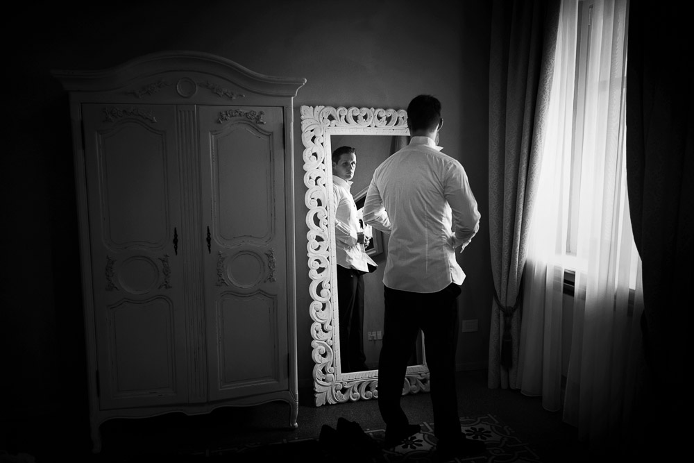 the groom is looking at the mirror