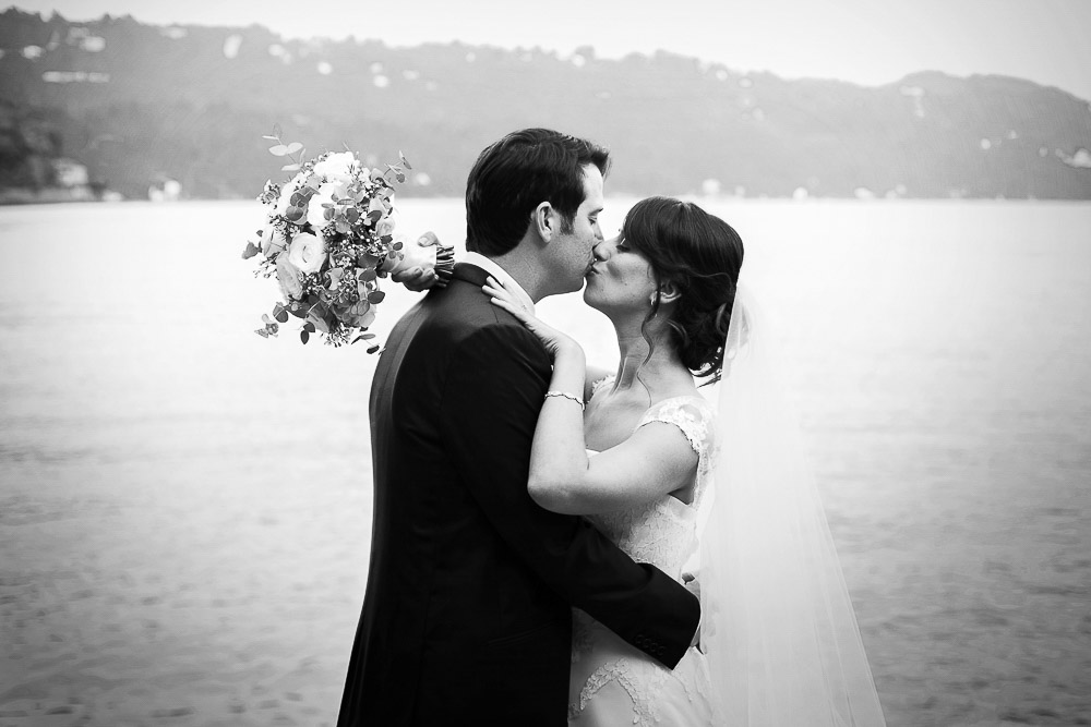 bride and groom kiss on jetty lake orta