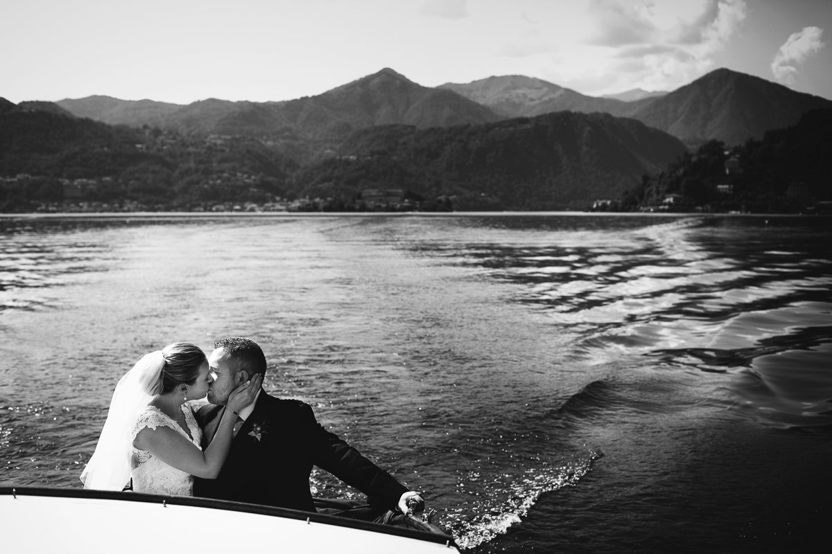 bride and groom kiss on boat lake orta