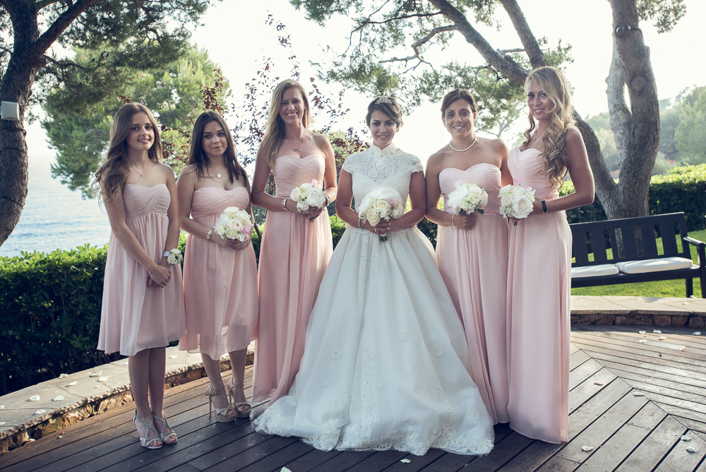 bride in white gown and bridesmaids with pink dresses holding bouquets