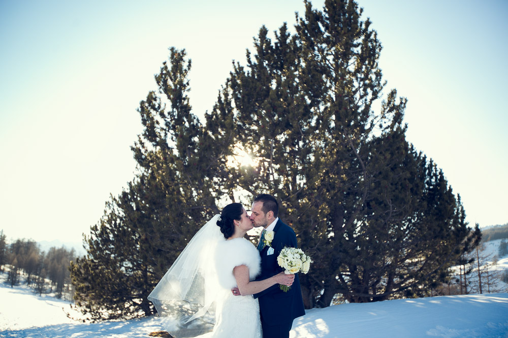 bride and groom kiss on snow