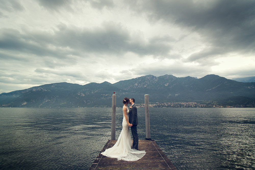 bride and groom kiss by the shores lake Como wedding