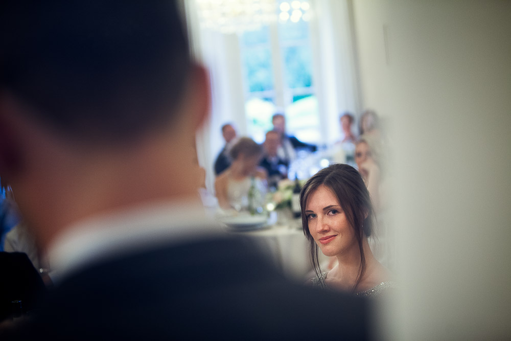 bride looks at the groom during speech