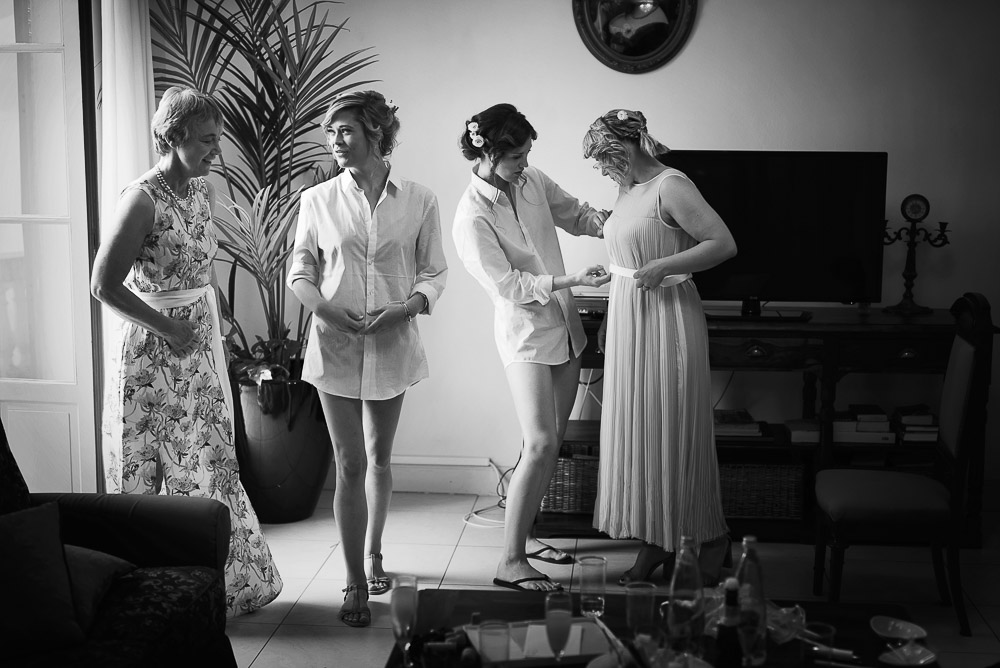 bride helps bridesmaids to get dressed
