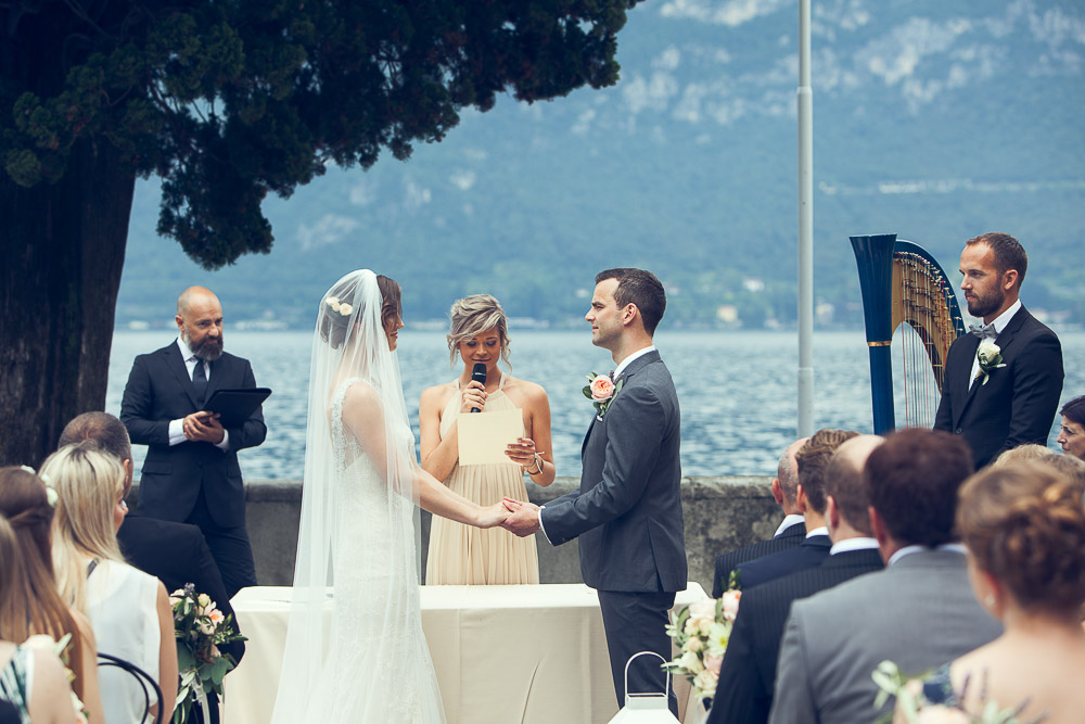 bride and groom holding hands by the lake
