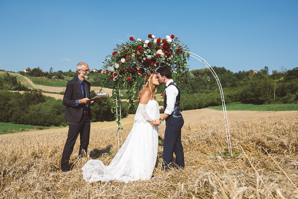 groom kisses her bride under a flower arch