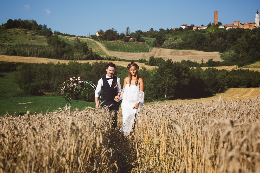 bride and groom walking in wheat meadows