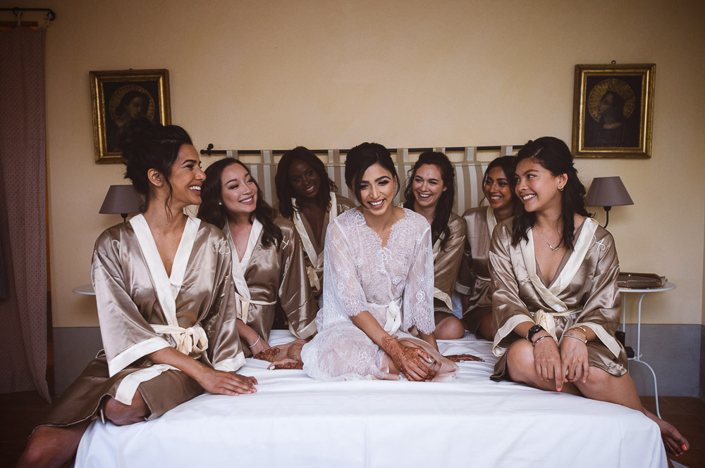 bride and bridesmaids on bed, Indian wedding in Tuscany